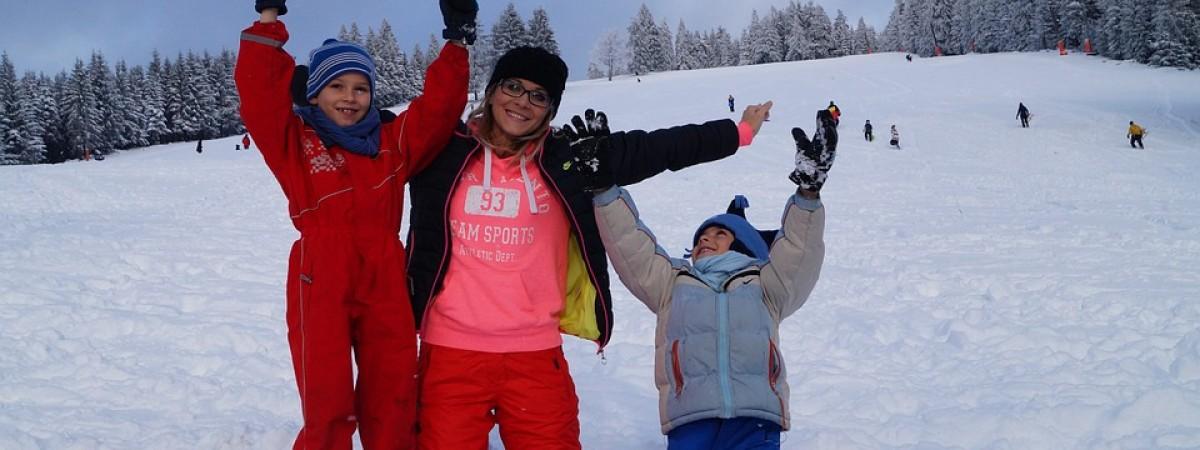 Madre esquiando con sus hijos
